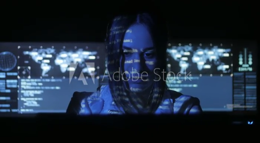 woman-hacker-programmer-is-working-on-computer-in-cyber-security-center-filled-with-display-screens-binary-code-on-her-face